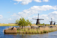Giant cradle and windmills in Kinderdijk, Holland. Giant baby cradle on a channel and historical windmills in Kinderdijk, Holland stock photography