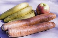 Giant Currots vs. banana and a big apple Royalty Free Stock Photos