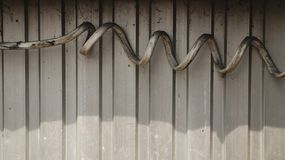Thick Dirty Spiral Electrical Wire on Corrugated Steel Wall royalty free stock photo
