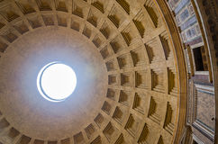 Giant dome of the Pantheon with a square pattern with a hole in the middle and the sunlight that makes its way into the church in. The capital of Italy Rome royalty free stock image