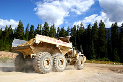 Giant Dump Truck. A giant dump truck hauling rocks during road construction in a forested area Royalty Free Stock Image