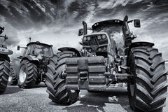 Giant farming tractors and storm clouds Stock Photos