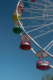 Giant Ferris Wheel Blue Sky Amusement Park PA. The vivid colored passenger gondolas, attached to the rim of a rotating upright wheel, lift riders 100 feet high Stock Images