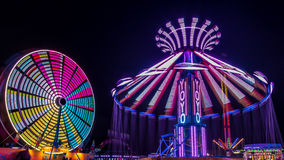 Giant Ferris Wheel and Yo-Yo Amusement ride. Side by side in night time shot with long exposure Stock Photo