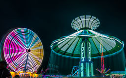 Giant Ferris Wheel and Yo-Yo Amusement ride. Side by side in night time shot with long exposure Stock Images