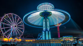 Giant Ferris Wheel and Yo-Yo Amusement ride. Side by side in night time shot with long exposure Royalty Free Stock Image