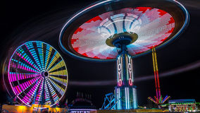 Giant Ferris Wheel and Yo-Yo Amusement ride. Side by side in night time shot with long exposure Royalty Free Stock Photography