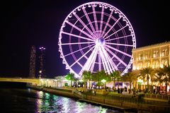 Giant Ferry Wheel and Water Canal in Park with blue sky background at Night royalty free stock images