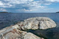 Giant foot. Stone coast of Ladoga lake, thunderclouds Royalty Free Stock Images