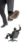 A giant foot. About to squish a businessman in a chair isolated on a white background Royalty Free Stock Images