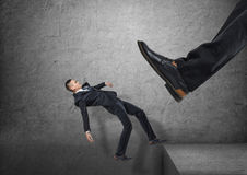 Giant foot in black shoe kicking little businessmen off the edge, and he is falling down. A giant foot in a black shoe kicking a little businessmen off the edge Royalty Free Stock Photo