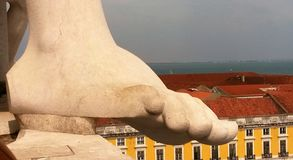 Giant foot on the roofs of Lisbon. Detail from Rua Augusta Arch terrace - May 2017 - Lisbon - Portugal royalty free stock photography