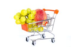 Giant fruits in a shopping cart, trolley on a white background. royalty free stock images