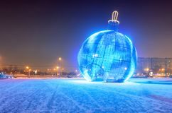 Giant glowing blue Christmas ball on the street. With snow Royalty Free Stock Photos