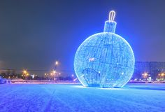 Giant glowing blue Christmas ball on the street with snow.  Royalty Free Stock Images