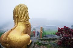 Giant gold statue of Singha Khmer, monk, and tourist in the mist stock image