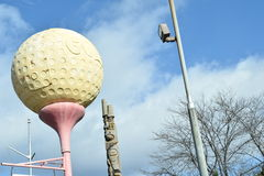 Giant Golf Ball Shaped Sign On Street Post.  Stock Photos