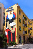 Giant graffiti of a fisherman with beard, kite and hat. Giant graffiti painted on the side of an apartments building in Civitavecchia, Italy Royalty Free Stock Image