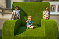 Giant green chair, National Theatre, Southbank, London. Children occupy the giant green chair outside London's Royal National Theatre, Southwark, London Stock Images