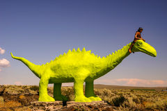 Giant Green Dinosaur. Tourist attraction at the Ice Caves in Shoshone, Idaho features a Shoshone Indian perched on the neck of a humongous lime green T-Rex Stock Photos