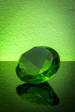 Giant green emerald on a green background Stock Photo