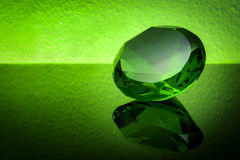 Giant green emerald on a green background Stock Photos