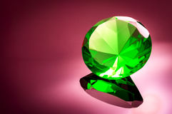 Giant green emerald on a red/ pink background. Surrounded by precious diamonds leading into the image Royalty Free Stock Photo