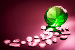 Giant green emerald on a red/ pink background. Surrounded by precious diamonds leading into the image Royalty Free Stock Images