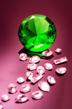 Giant green emerald on a red/ pink background. Surrounded by precious diamonds leading into the image Royalty Free Stock Image