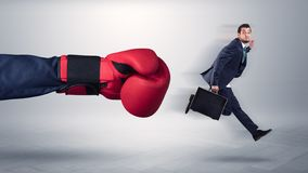 Giant hand gives a kick to a small businessman. Giant hand gives a kick to a small employee businessman royalty free stock photo