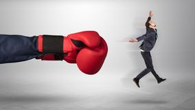 Giant hand gives a kick to a small businessman. Giant hand gives a kick to a small employee businessman royalty free stock image