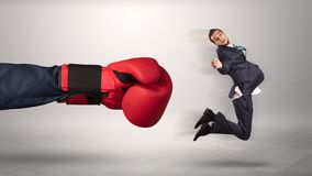 Giant hand gives a kick to a small businessman. Giant hand gives a kick to a small employee businessman stock photos