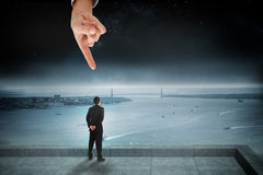 Giant hand pointing at businessman standing and looking Stock Image