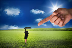 Giant hand pointing at young businesswoman holding umbrella Stock Photo