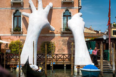Giant hands rise from the Grand Canal in Venice Stock Photography