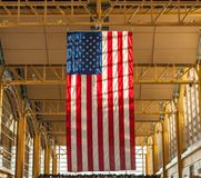 Giant hanging US Flag at Airport. The American flag hangs in the afternoon sun in this US airport in Washington DC. in a modern designed terminal Stock Images