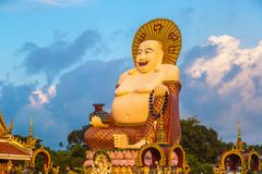 Giant happy buddha Samui. Giant smiling or happy buddha statue in Wat Plai Laem Temple, Samui, Thailand in a summer day royalty free stock photo