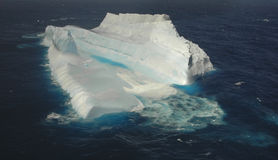 Giant iceberg in the southern ocean. Aqua waves wash over a giant iceberg in the southern ocean as it floats into New Zealand waters, global warming is blamed Royalty Free Stock Image