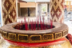 Giant joss stick pot with red incense sticks stock image