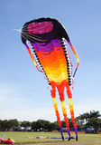 Giant Kite. Giant colorful kite in the shape of a long catapillar like creature leaving the ground Stock Photos