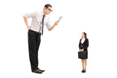 Giant man looking at woman through magnifier Stock Images