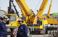 Giant mobile cranes and building workers Royalty Free Stock Photography