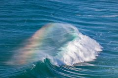 Giant Ocean Wave with Rainbow in Spray Stock Image