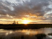 Sunset in the swamps. Giant orange sun sets behind the bayou of a cypress swamp and reflects in the river stock photo