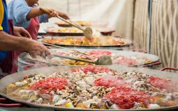 Giant paella in preparation. Added tomatoes and seafood. People mix in pans paella with tomato sauce royalty free stock images