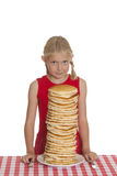 Giant Pancake Breakfast. Little girl with a giant plate of pancakes, a knife and fork on a table cloth Royalty Free Stock Photography