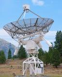 Giant parabolic antenna looking into blue sky Stock Image