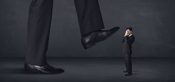 Giant person stepping on a little businessman concept Stock Images