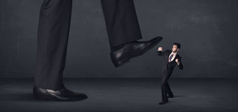 Giant person stepping on a little businessman concept Royalty Free Stock Photos