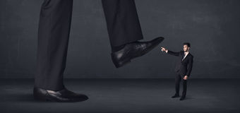 Giant person stepping on a little businessman concept Stock Photo